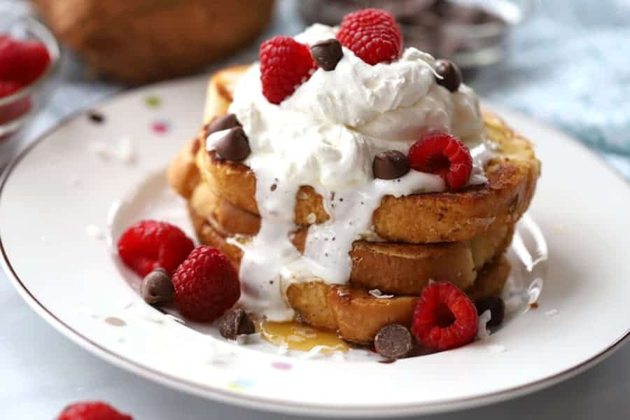coconut french toast with whipped cream, berries and chocolate chips