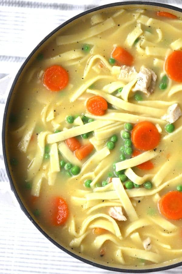 homemade chicken noodle soup with pea and carrots in a large pot