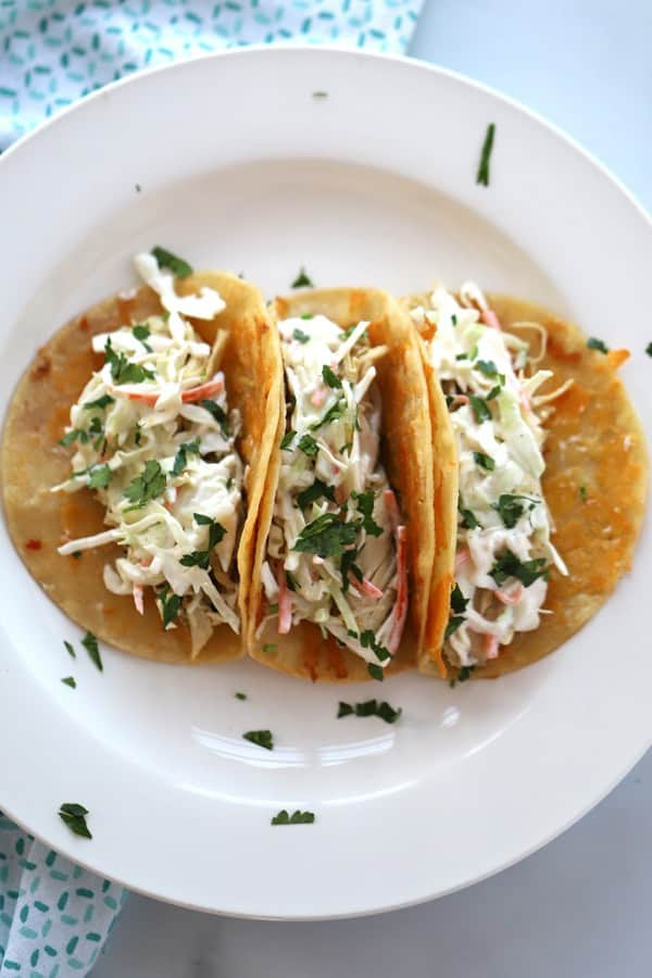 Three tortilla shells filled with cilantro lime chicken and toppings on a white plate.
