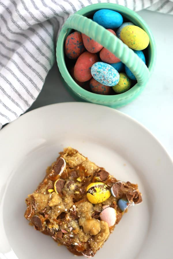 Chocolate Chip Cookie Bar on a white plate with a little basket of easter eggs