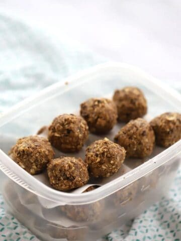 Energy balls in a plastic tupperware container.