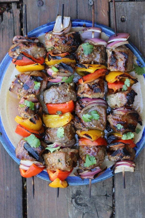 Asian Beef Steak kabobs on a blue platter