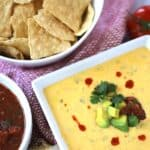 Cheddar queso dip in a bowl served with chips on the side
