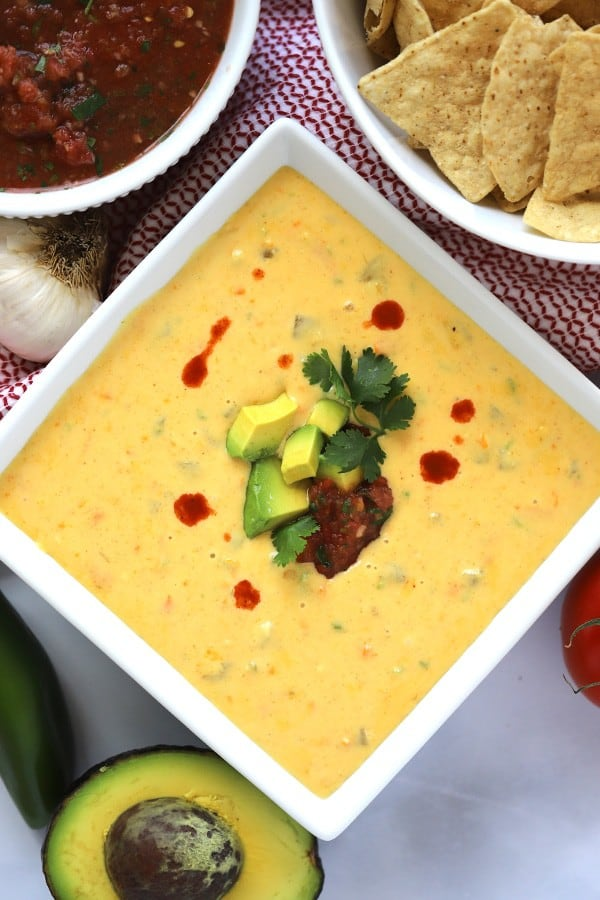 Cheddar Queso Dip with chips on the side and hot sauce with avocado garnish
