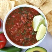 fresh salsa ingredients in a serving bowl with chips and avocado