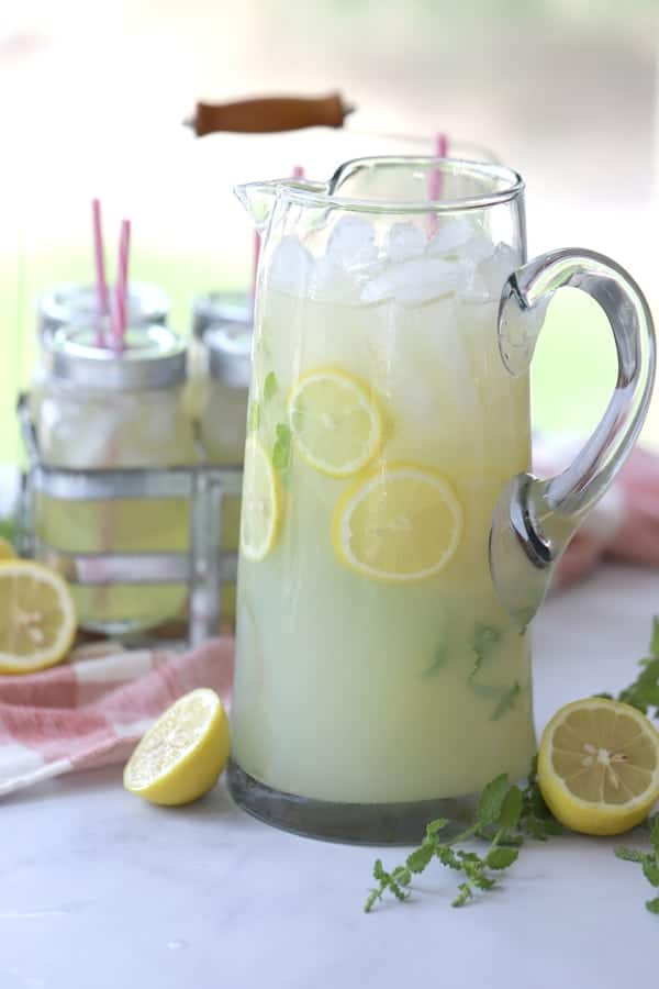 Mint lemonade in a tall clear pitcher with lemons and mint as garnish