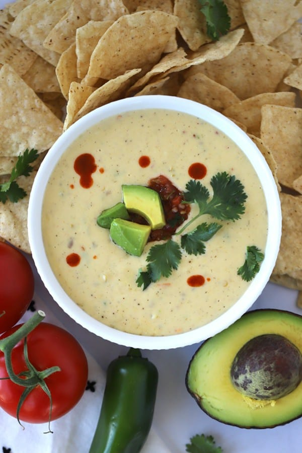 Creamy pepper jack queso in a white serving dish with chips, avocado, and tomatoes