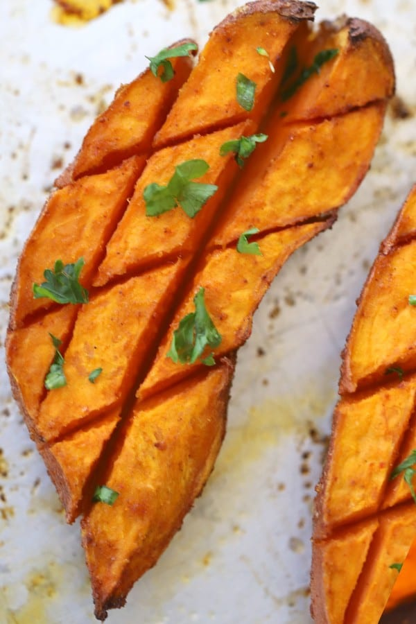Roasted sweet potatoes that have been scored and garnished with fresh herbs.
