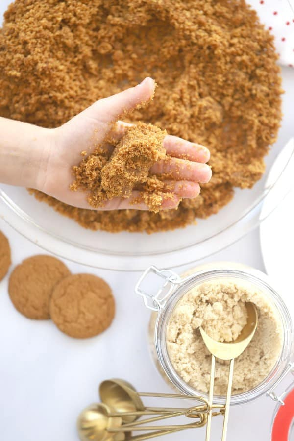 A bowl of gingersnap crust mixture with a hand holding some and more ingredients in the background.