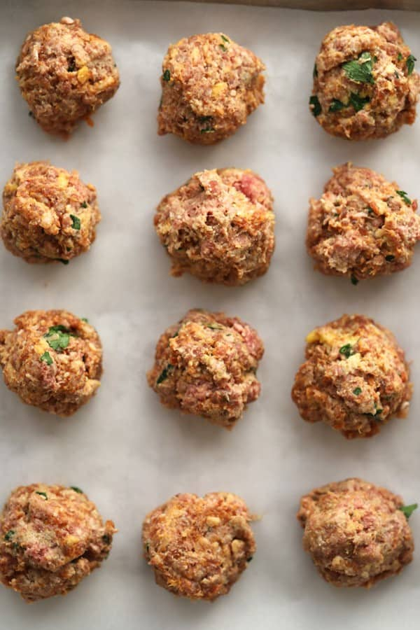raw meatballs on a baking sheet