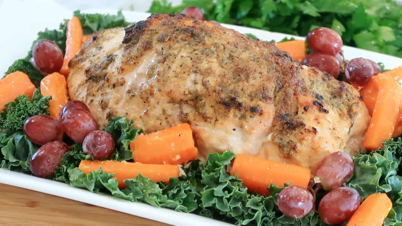 oven roasted turkey on a white platter with kale, grapes and cooked carrots