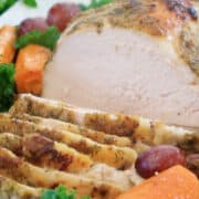 Herb Crusted Turkey breast sliced and on a white platter
