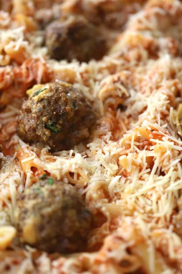Meatballs covered in cheese on a penne pasta bake