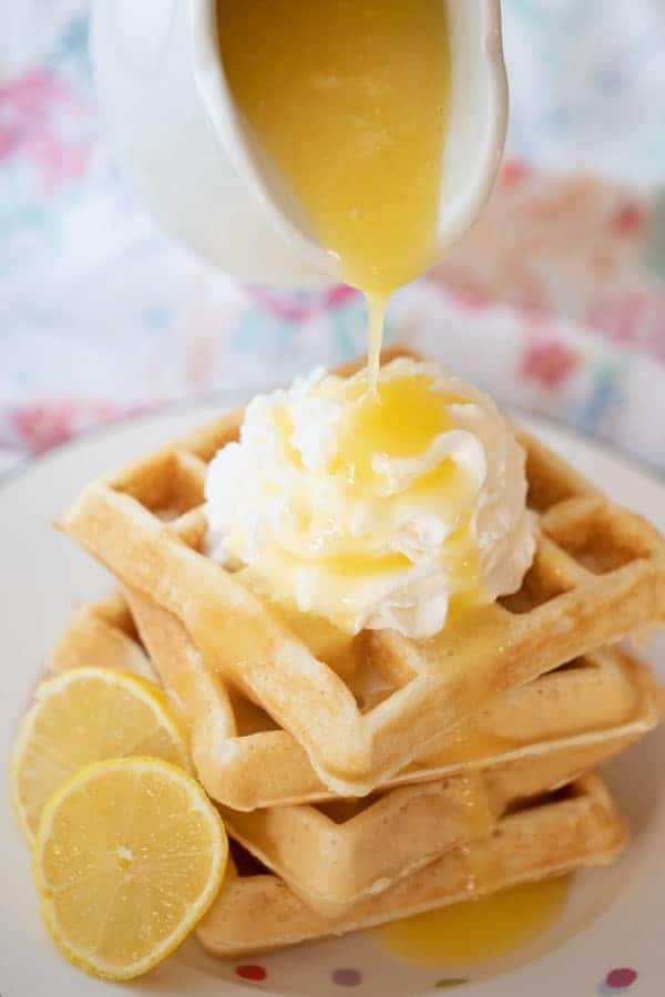 lemon syrup recipe being poured over waffles and whipped cream