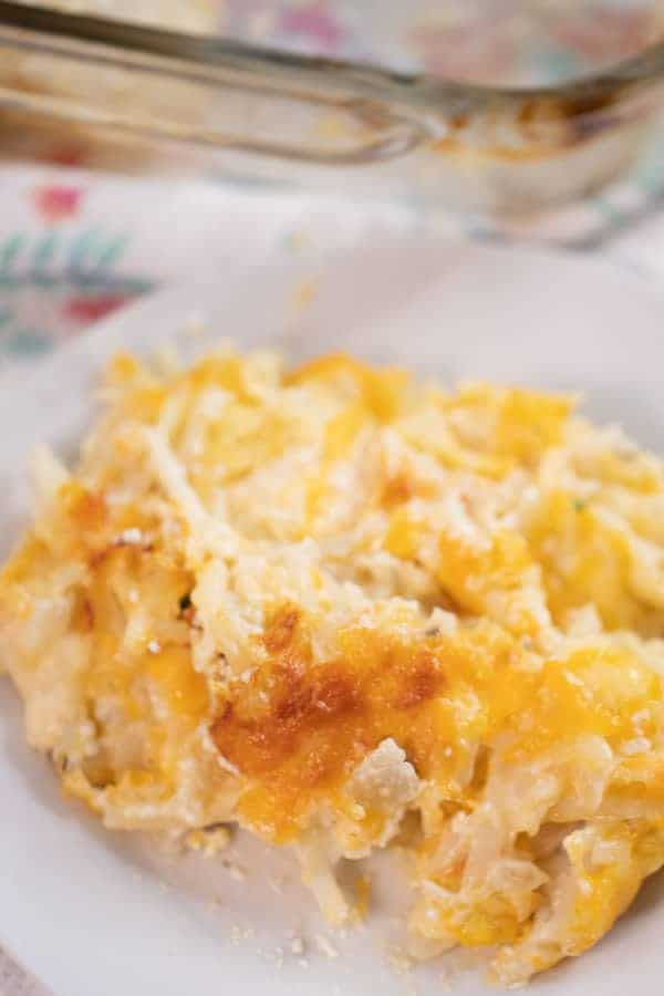 cheesy potato casserole serving on a white plate