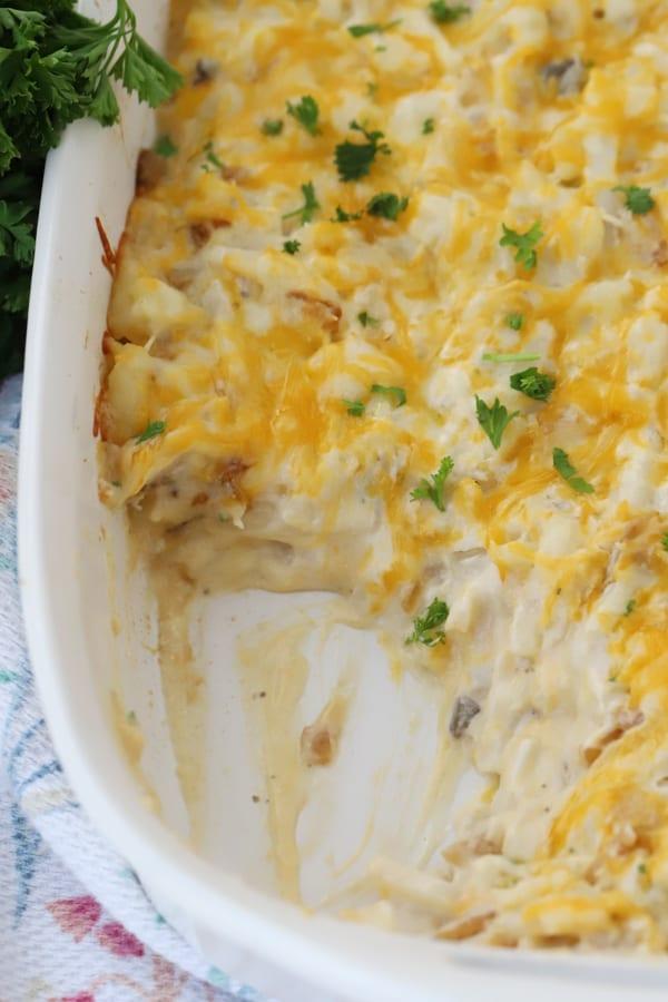 cheesy potato casserole in a white baking dish
