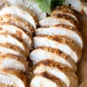 best baked chicken breast on a wood cutting board