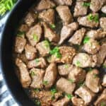 garlic butter steak bites in a pan with parsley