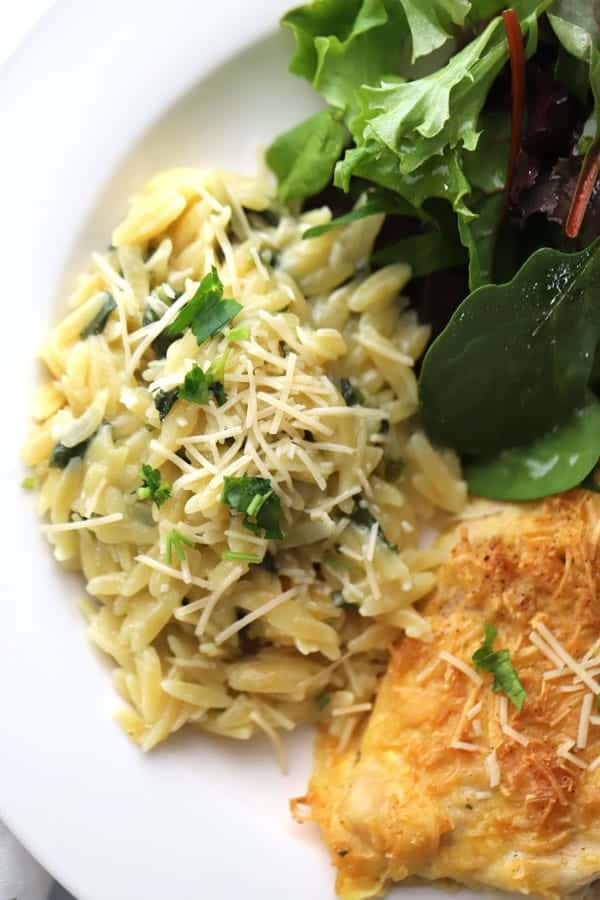 parmesan Orzo on a plate with salad and chicken