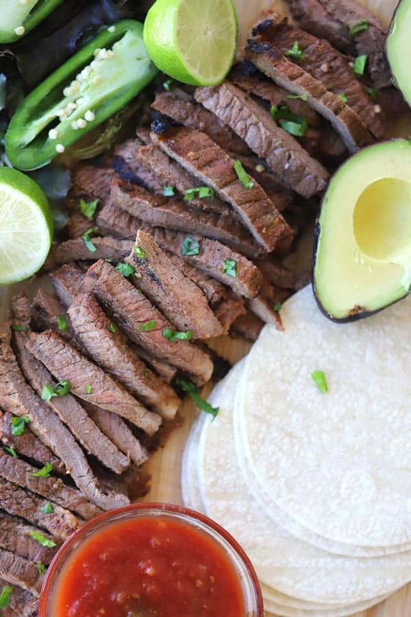 authentic carne asada with taco toppings on a cutting board
