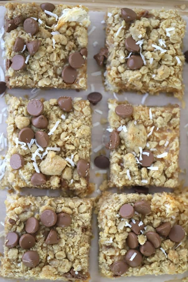 Coconut Caramel Magic Bars on a cutting boars