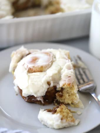 einkorn cinnamon roll on a white plate with frosting