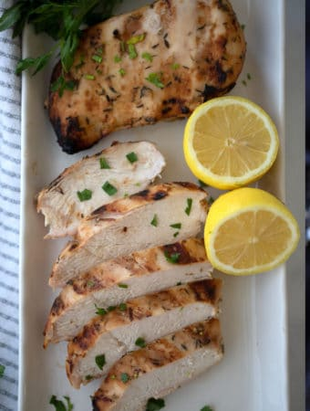 honey mustard chicken with a lemon wedge on a white plate