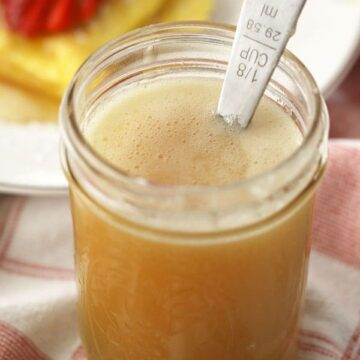 HOmemade Buttermilk syrup recipe a mason jar on a breakfast table.