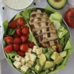Healthy grilled chicken salad in a bowl with a side of pesto ranch.