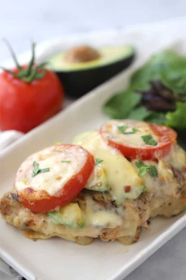 grilled california chicken on a white plate, topped with tomatoes, cheese and fresh herbs.