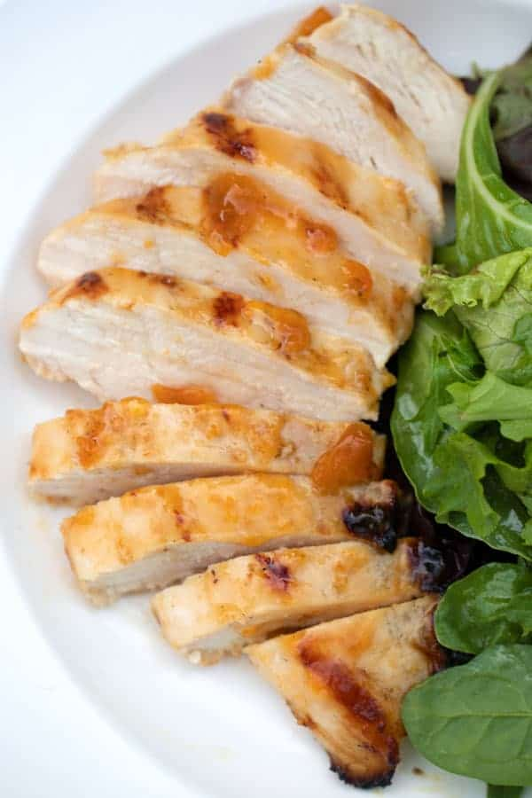 Grilled Apricot Chicken on a white plate with green salad