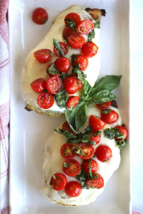 grilled caprese chicken topped with cherry tomatoes and fresh mozzerella