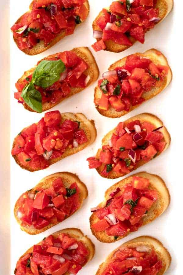 Tomato and basil bruschetta lined up on a serving platter.