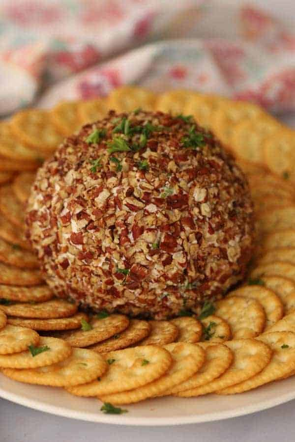 Ham and Cheddar Cheese Ball on a serving tray with Ritz Crackers.