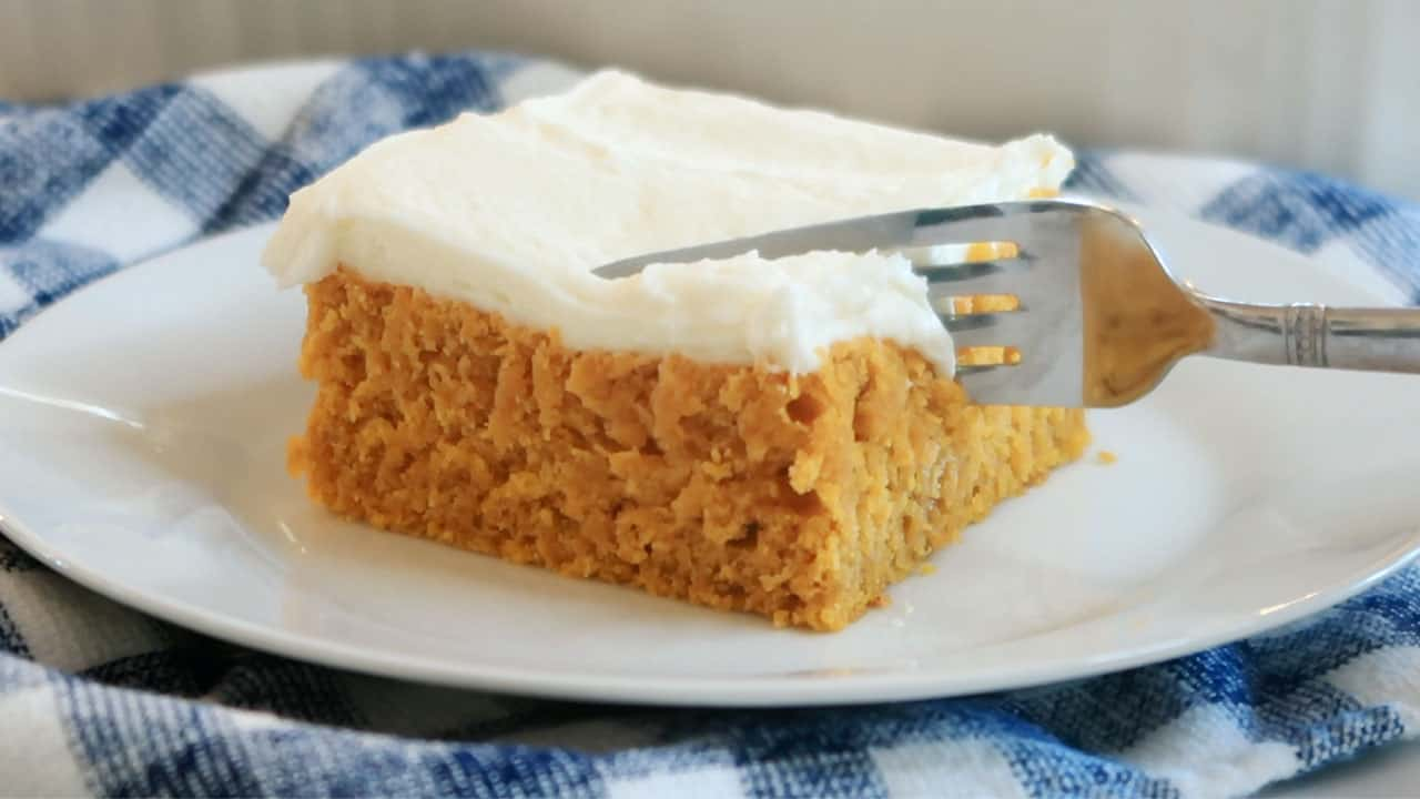 pumpkin cake with cream cheese frosting being cut with a fork