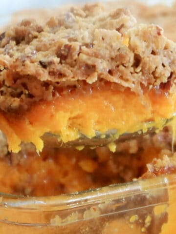 a big scoop of sweet potato casserole with pecan crumble topping