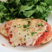 oven baked chicken parmesan on a plate with salad