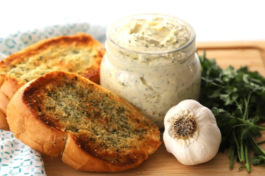 garlic butter and garlic bread on a cutting board