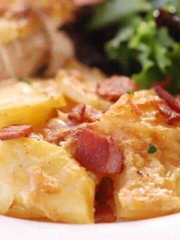 The best scalloped potatoes on a plate with chicken and a green salad