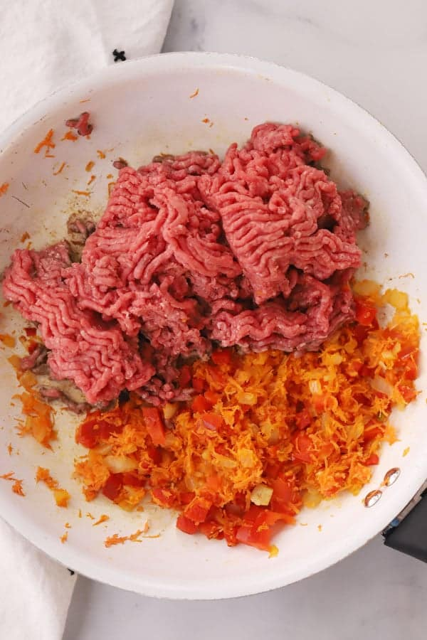 raw ground beef, carrots, bell peppers and onions in a saute pan