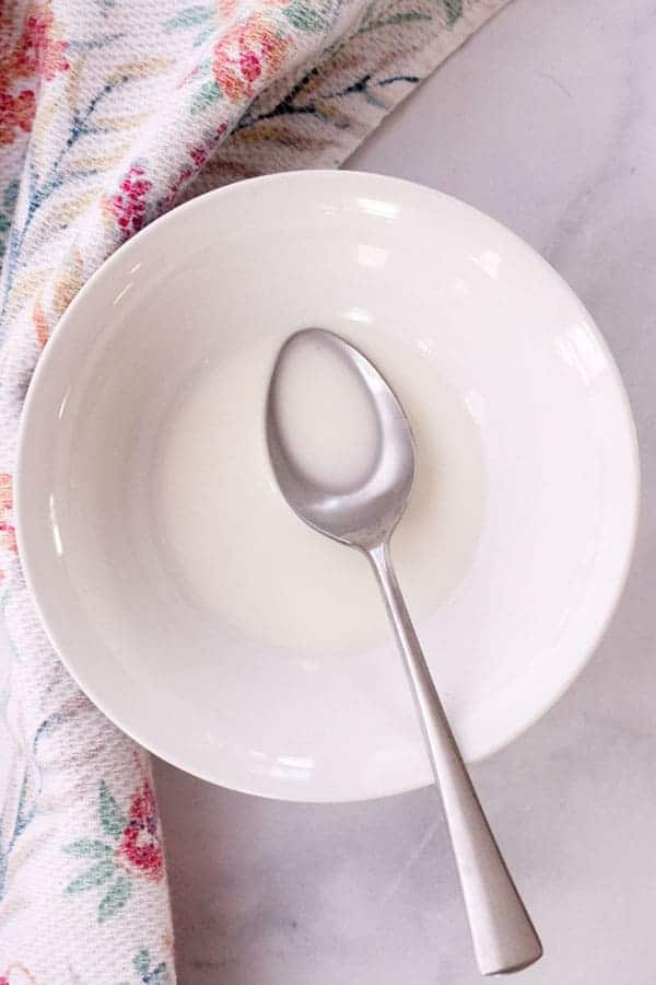 cornstarch slurry in a white bowl being mixed with a spoon