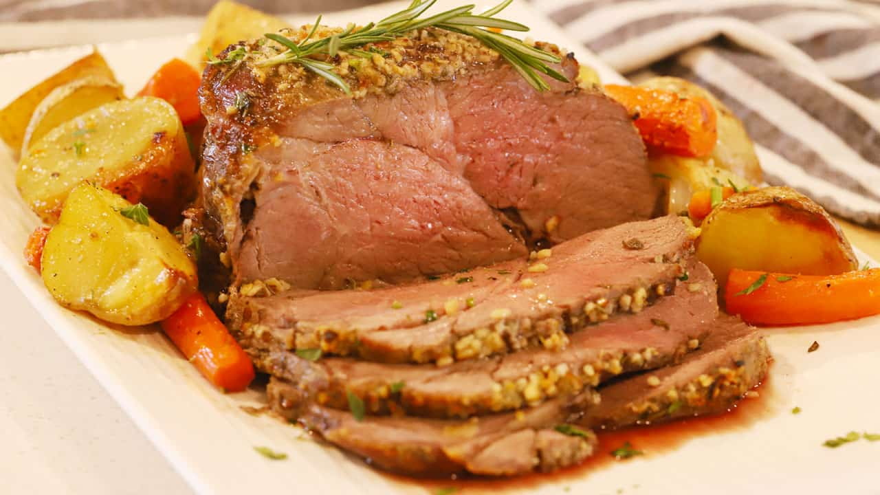sliced herb crusted top round roast beef on a plate with roasted potatoes and carrots