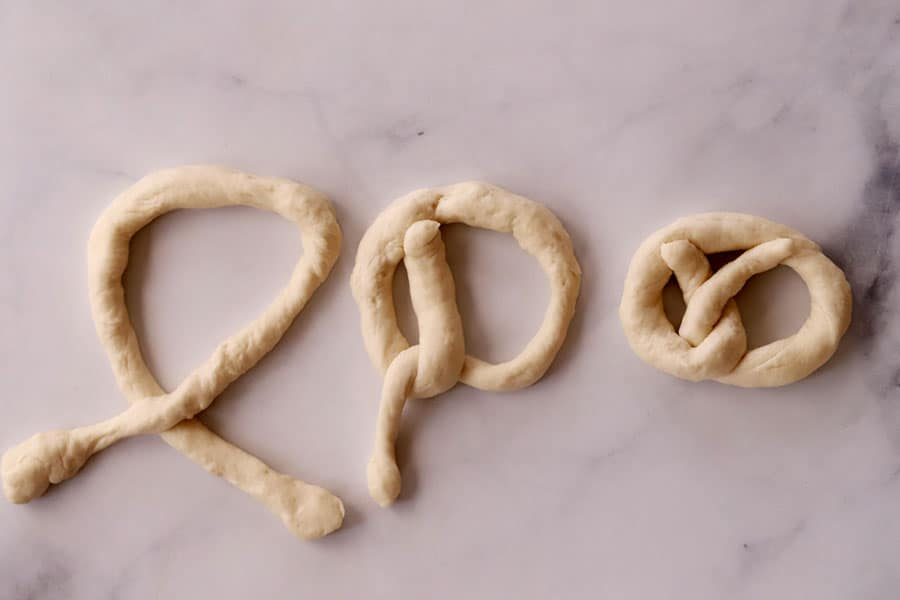 pretzel dough being shaped on a marble slab