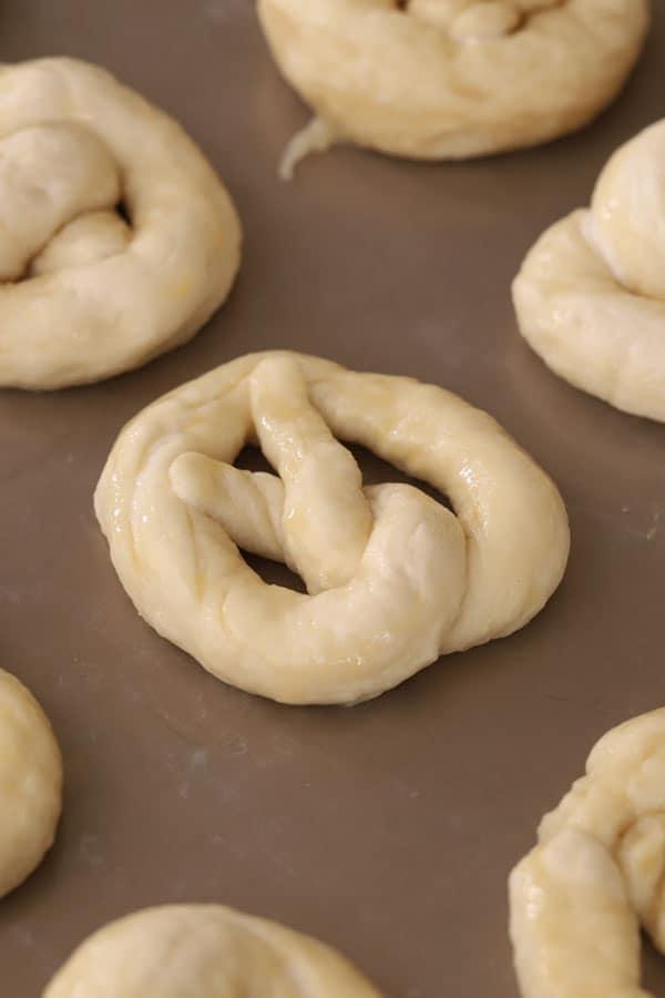 raw soft pretzels on a baking sheet