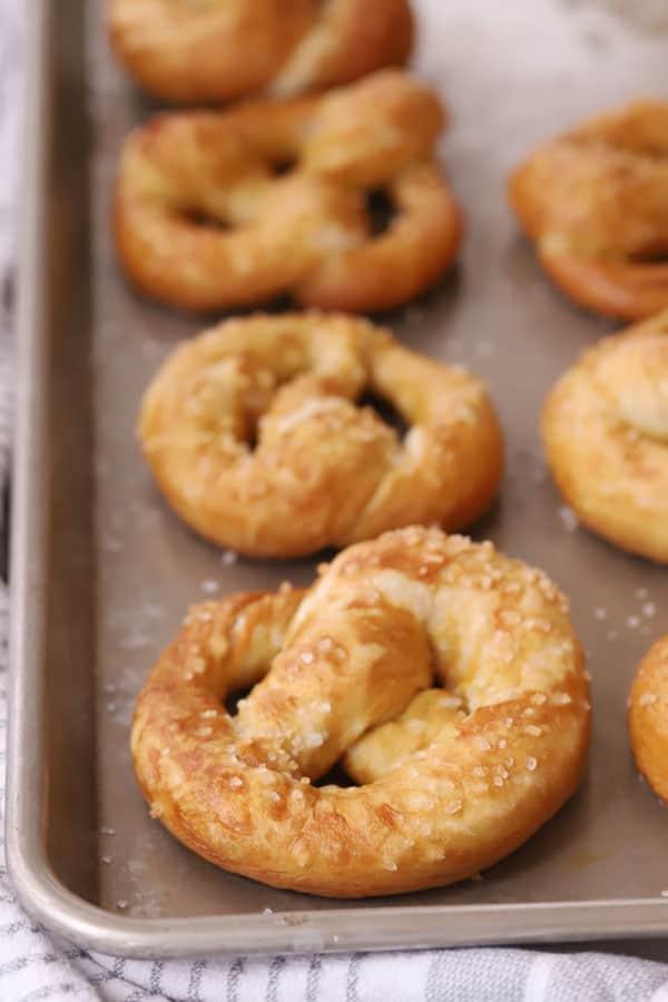 Homemade soft pretzels on a baking sheet.