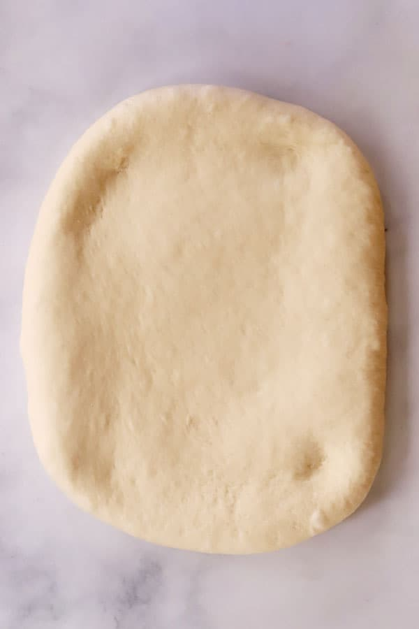 white bread dough rolled out into a rectangle