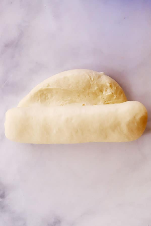 white bread dough being rolled into a loaf shape
