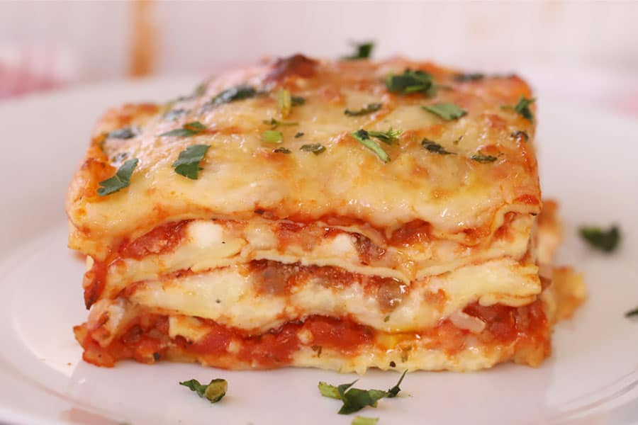 slice of baked lasagna on a plate garnished with chopped parsley