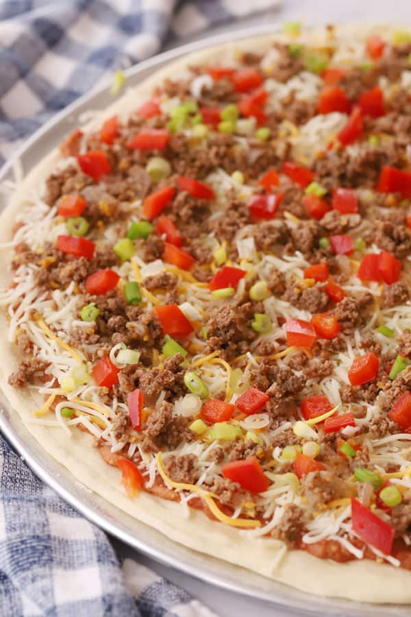 taco pizza covered with toppings and ready to bake