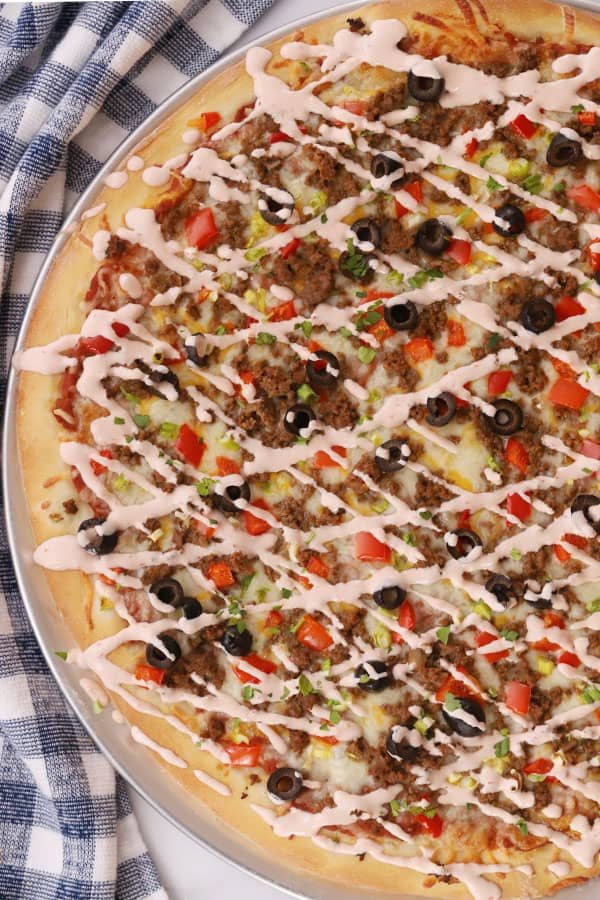 Taco pizza on a table drizzled with sauce.
